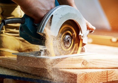 building contractor worker using hand-held worm drive circular saw cut boards